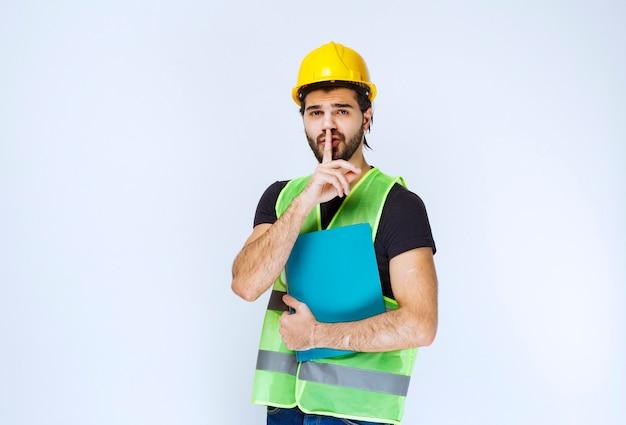 파란색 폴더가 있는 노란색 헬멧을 쓴 남자는 졸리고 차분해 보입니다.