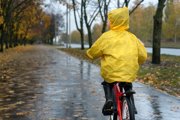Мужчина в желтом плаще едет по аллее в осеннем парке. мальчик едет на велосипеде по городу под дождем. вид сзади.