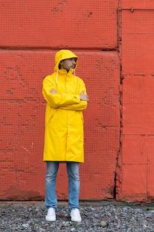 빨간 벽 근처에 서있는 노란 우비에 남자