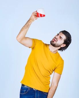 黄色いシャツを着た男性は、コーヒーマグが空になっていることに気づきました。