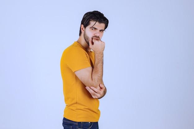 魅惑的で魅力的なポーズを与える黄色いシャツの男。