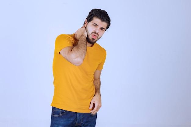매혹적인 매력적인 포즈를 취하는 노란색 셔츠를 입은 남자.