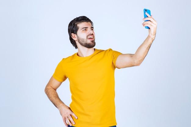 青いスマートフォンを持っている黄色いシャツの男。