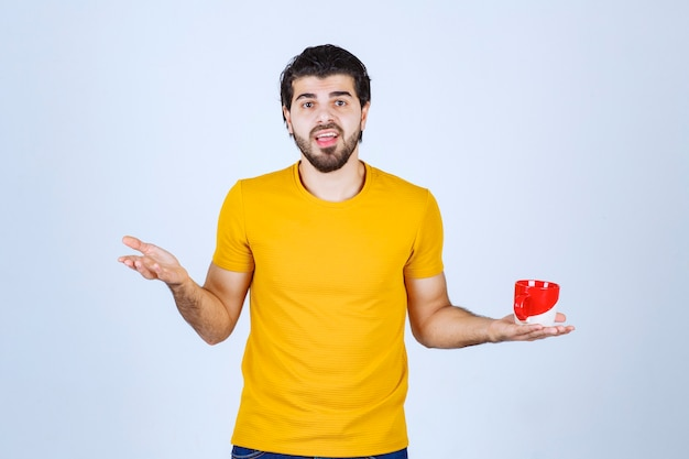 赤いカップを持って考えている黄色いシャツの男。 無料写真