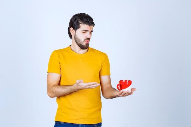赤いカップを持って考えている黄色いシャツの男。