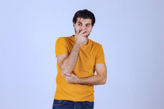 노란색 셔츠를 입은 남자는 의심스럽고 생각합니다.