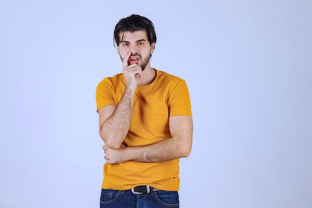 노란색 셔츠를 입은 남자는 의심스럽고 생각한다.