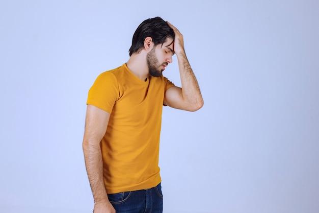 黄色いシャツを着た男は疑わしく、考えているように見えます