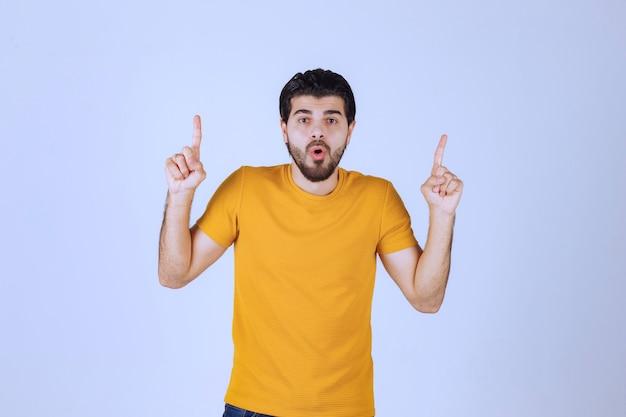 Мужчина в желтой рубашке выглядит напуганным и взволнованным.