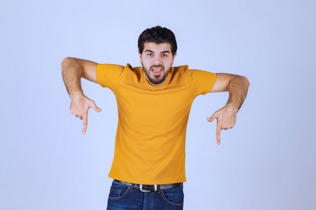 아래를 가리키는 노란색 셔츠에 남자입니다.