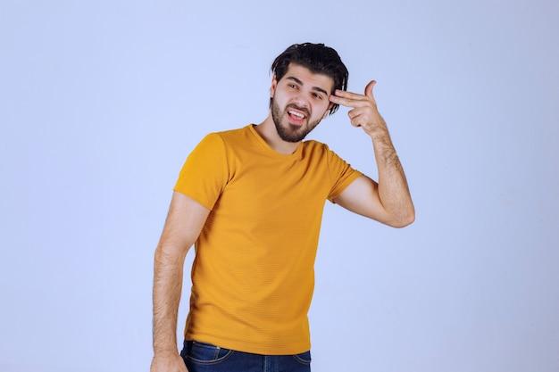 手に銃のサインを示す黄色いシャツの男