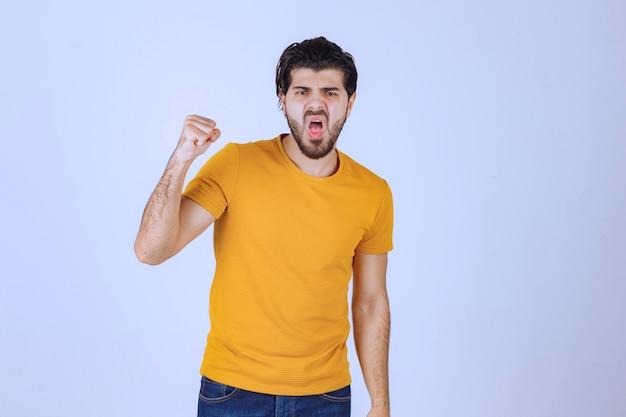 Человек в желтой рубашке показывает свой кулак и силу.