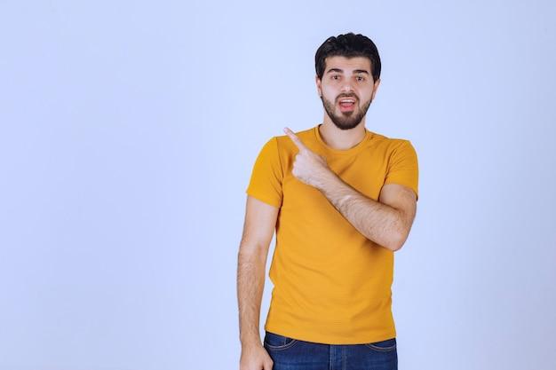 왼쪽에 뭔가 보여주는 노란색 셔츠에 남자.