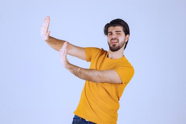 Человек в желтой рубашке что-то останавливает
