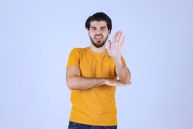 뭔가 중지하는 노란색 셔츠에 남자