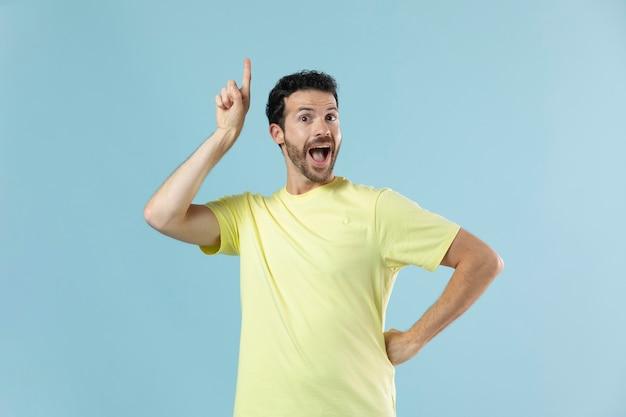 Человек в желтой футболке позирует для студийного портрета