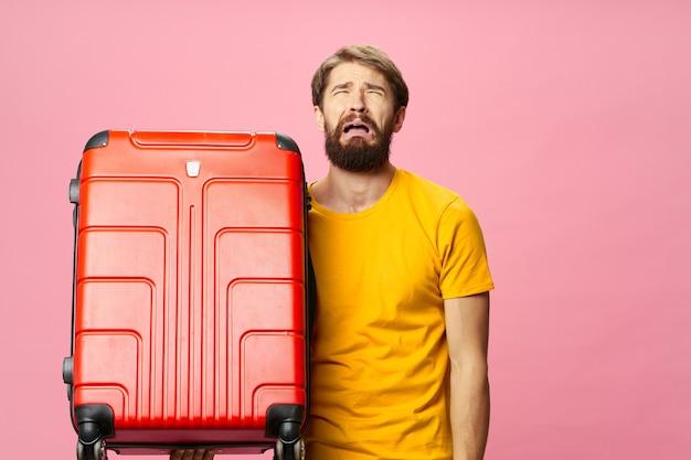 ピンクの背景の旅行観光に赤いスーツケースと黄色のtシャツの男