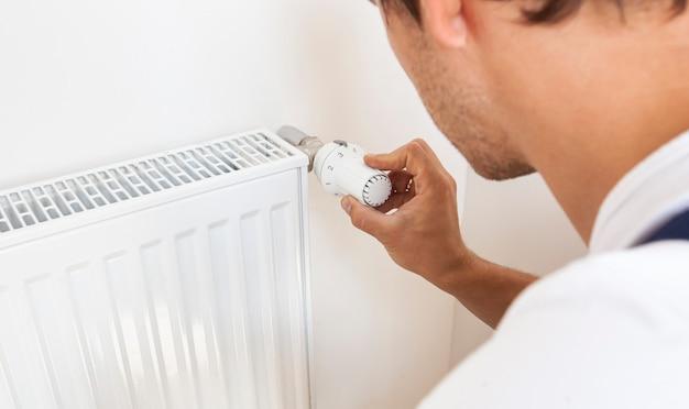 Человек увеличивает температуру радиатора, регулируя термостат