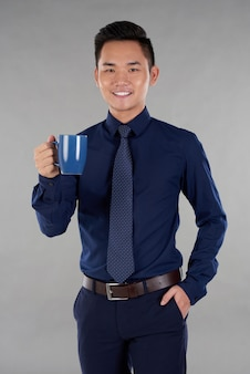Man indark blue formalwear standing against grey background with navy blue mug of tea