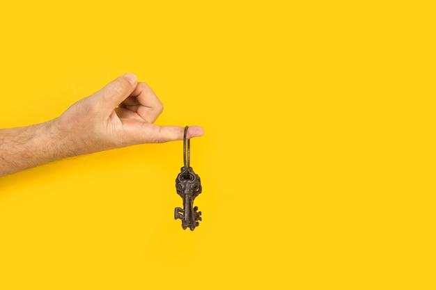 Указательный палец человека держит богато украшенные железные ключи на желтом