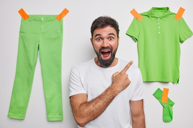 Man indicates at clothing with glad expression attracts your attention to items for green clothes demonstrates something