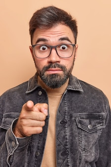 Man indicates forward at something terrible has bugged eyes terrified expression dressed in denim jacket isolated on beige