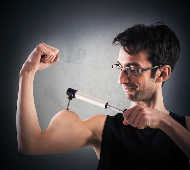 男はポンプで筋肉を膨らませる