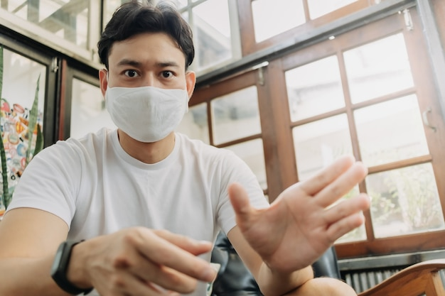 Man influencer with mask is talking with his camera in a cafe