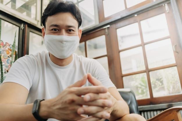 マスクをした男性インフルエンサーがカフェで彼のカメラと話している