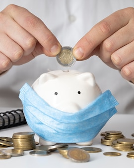 Man inserting a coin in a piggy bank with a medical mask