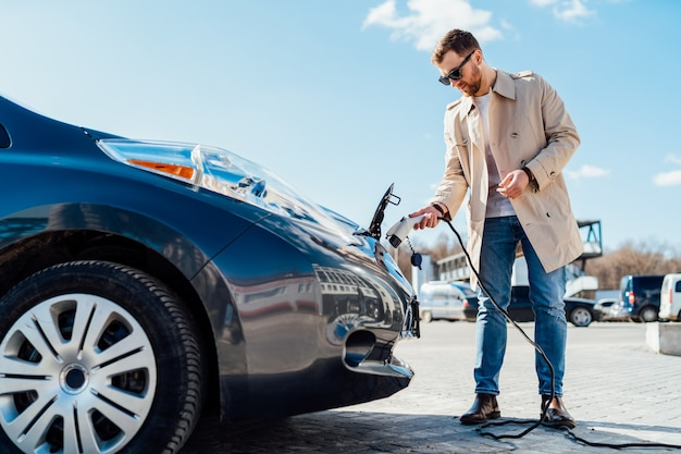 Man inserts the charging cable into the socket of electric car