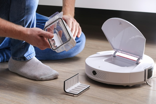 A man inserts a filter and a container to collect dust and debris into a robot vacuum cleaner.