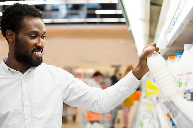 Мужчина проверяет бутылку молока в продуктовом магазине