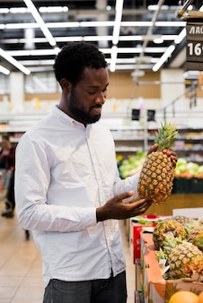 Man inspecting pineapple in grocery store