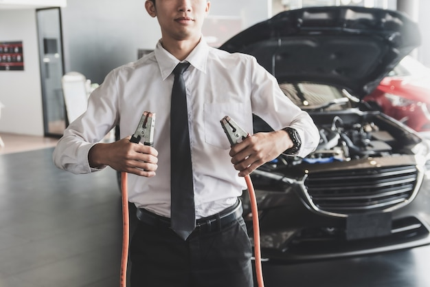 Man inspection holding jumper cables for charger battery service maintenance of car