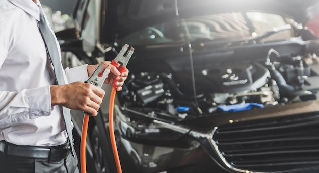 Man inspection holding jumper cables for charger battery service maintenance of industrial to engine repair.in factory transport automobile automotive image