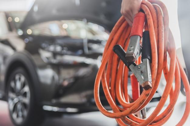 Человек осмотр держит перемычки для зарядного устройства сервисное обслуживание аккумуляторов от промышленного до ремонта двигателя.