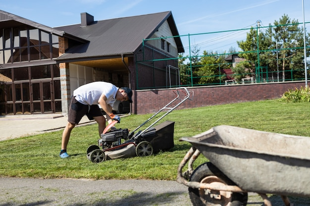 Man inspects the engine of a gasoline lawn mower before mowing the grass