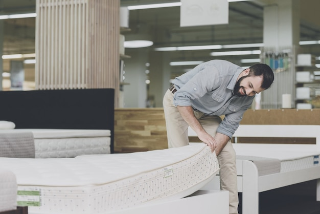 A man inspects a mattress in a mattress store.