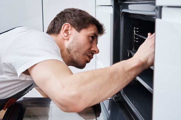 Man installing electricity oven in the kitchen