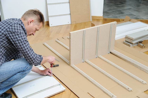 Man installing joint connector bolts in the furniture board