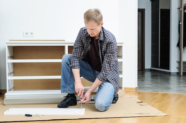 Мужчина устанавливает соединительные болты в мебельную доску