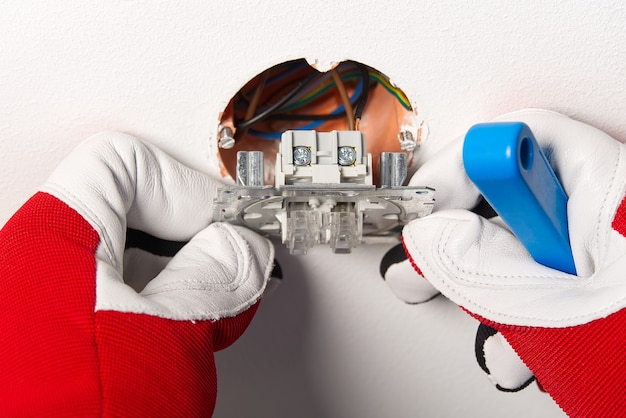 Man installing light switch after home renovation. electrician installing light switch on painted wall with screwdriver
