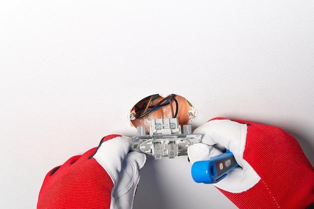 リフォーム後に電灯のスイッチを設置する男性