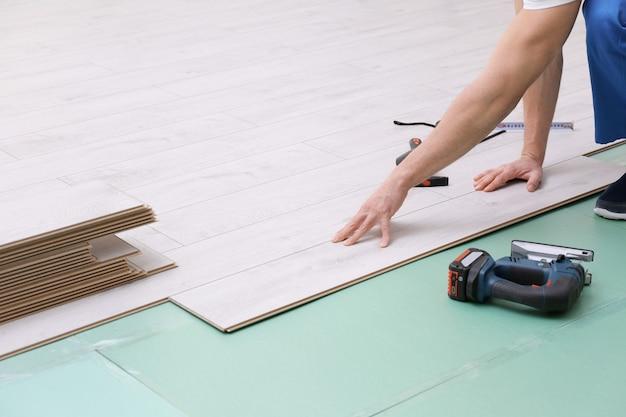 Мужчина устанавливает новый деревянный пол из ламината