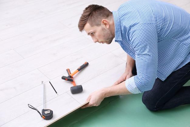 새로운 나무 라미네이트 바닥재를 설치하는 남자