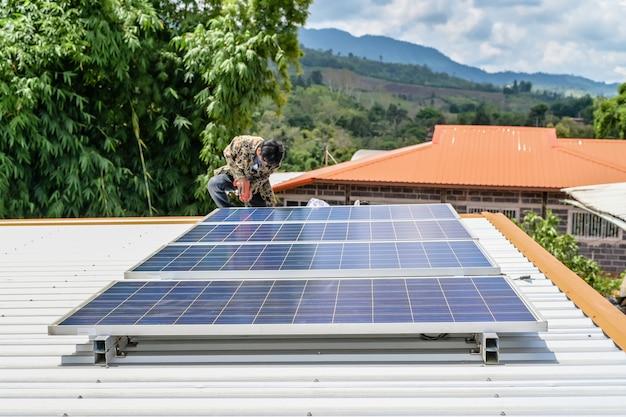 代替エネルギー太陽光発電の安全なエネルギーのために屋根の家にソーラーパネルを設置する男。自然からの電力太陽光発電太陽電池発電機は地球を救う