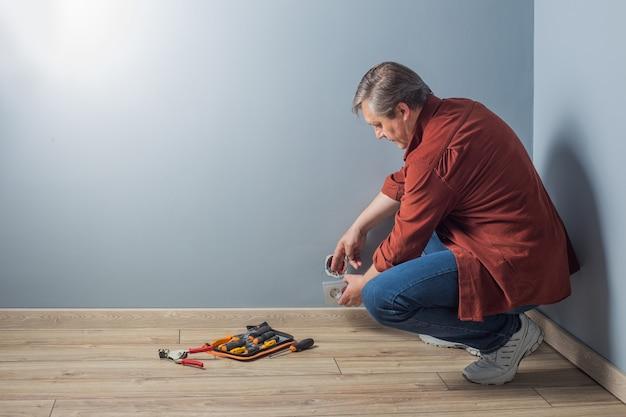 남자는 회색 벽에 전기 콘센트를 설치