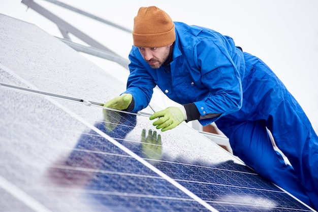 Человек устанавливает солнечные батареи