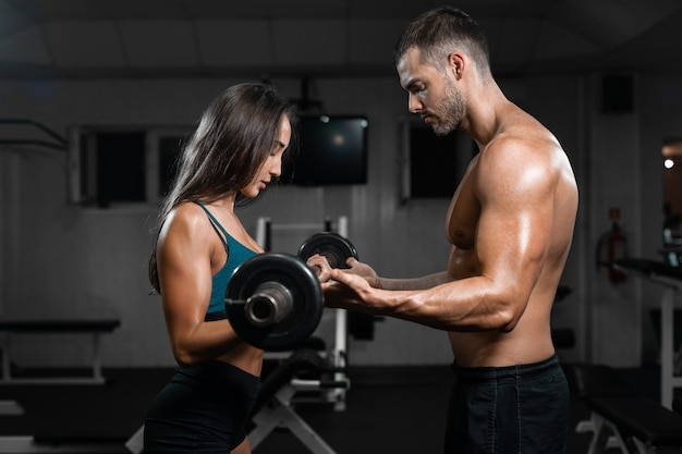 Man instructor and woman train, lifting dumbbells